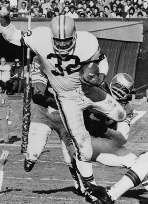 Cleveland Browns halfback Jim Brown carries the ball past Philadelphia Eagles defenders in a game from the 1964 NFL championship season