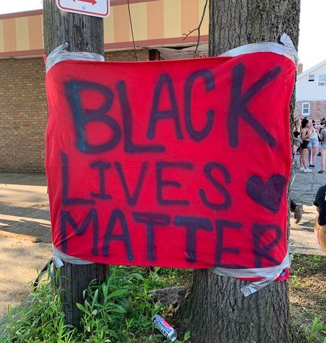 A Black Lives Matter sign hangs next to the West Mini Mart.