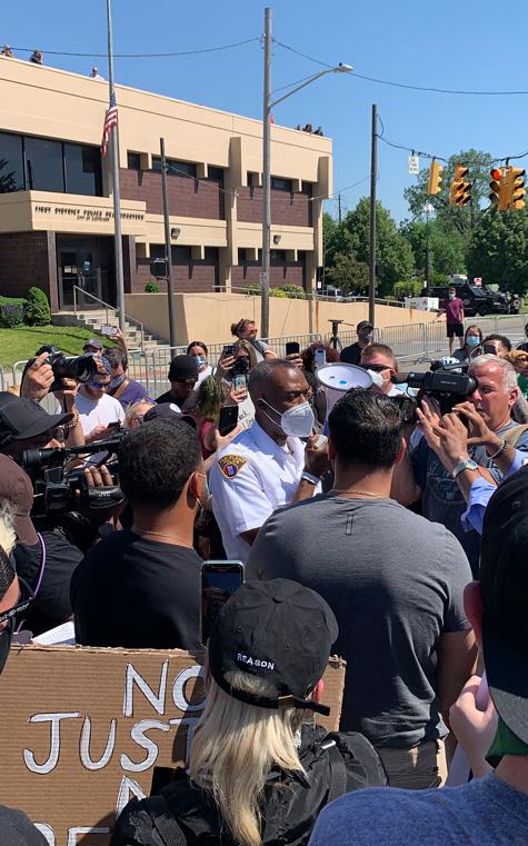 Deputy Chief Wayne Drummond talking to a crowd of protestors.